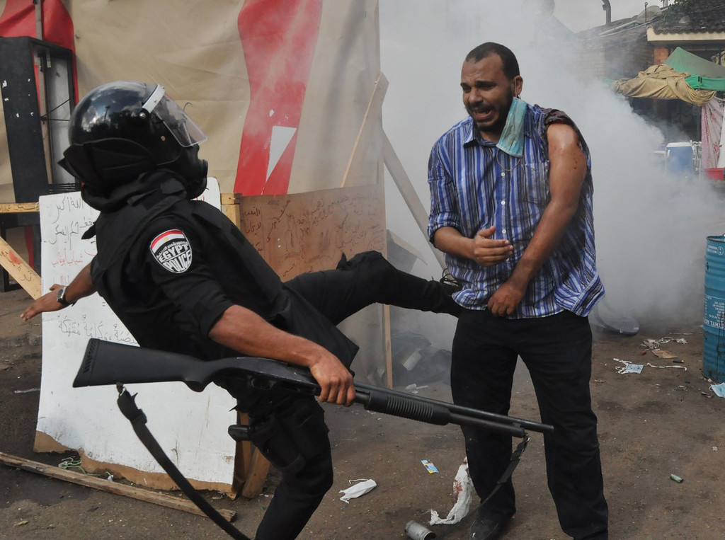 . An Egyptian security force kicks a supporter of ousted Islamist President Mohammed Morsi as they clear a sit-in camp set up near Cairo University in Cairo\'s Giza district, Egypt, Wednesday, Aug. 14, 2013.  (AP Photo/Hussein Tallal)