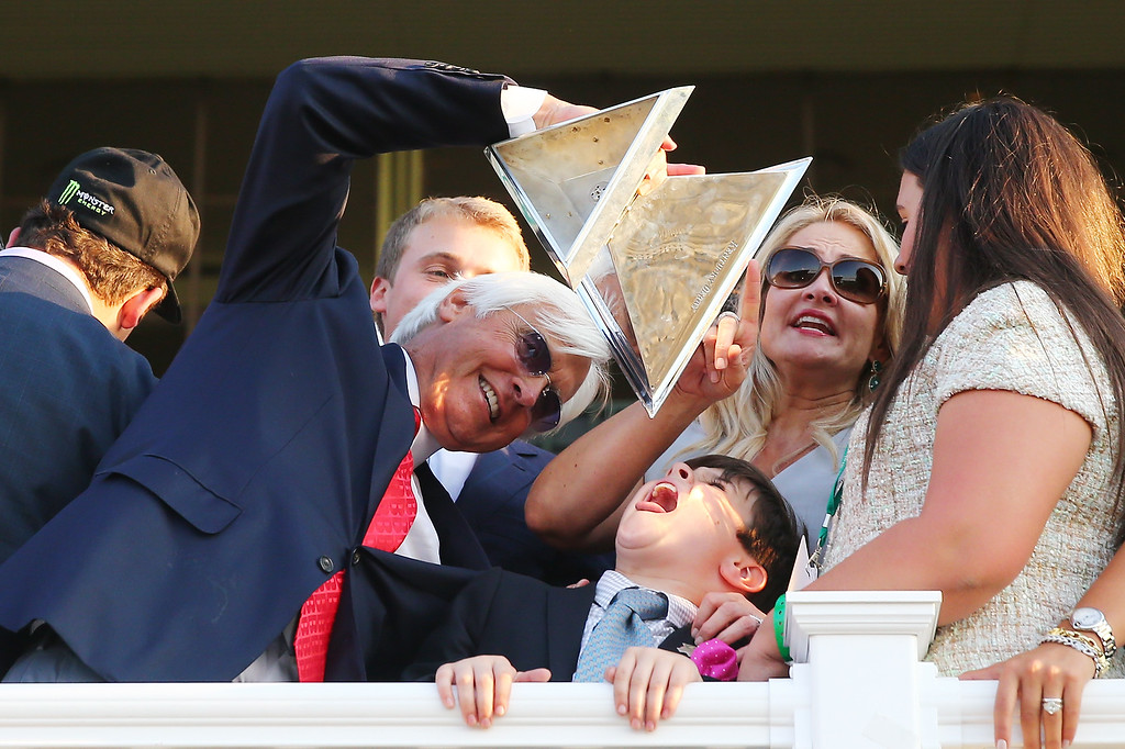 . Bob Baffert, trainer of American Pharoah #5, celebrates as his son Bode looks on after winning the 147th running of the Belmont Stakes at Belmont Park on June 6, 2015 in Elmont, New York. With the wins American Pharoah becomes the first horse to win the Triple Crown in 37 years.  (Photo by Elsa/Getty Images)