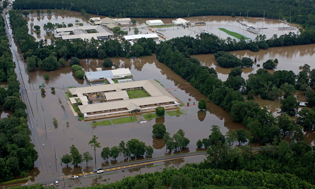 . This aerial photo over Hammond, La., shows flooded Hammond Eastside Elementary Magnet School and Hammond High Magnet School after heavy rains inundated the region Saturday, Aug. 13, 2016. Louisiana Gov. John Bel Edwards says more than 1,000 people in south Louisiana have been rescued from homes, vehicles and even clinging to trees as a slow-moving storm hammers the state with flooding. (AP Photo/Max Becherer)