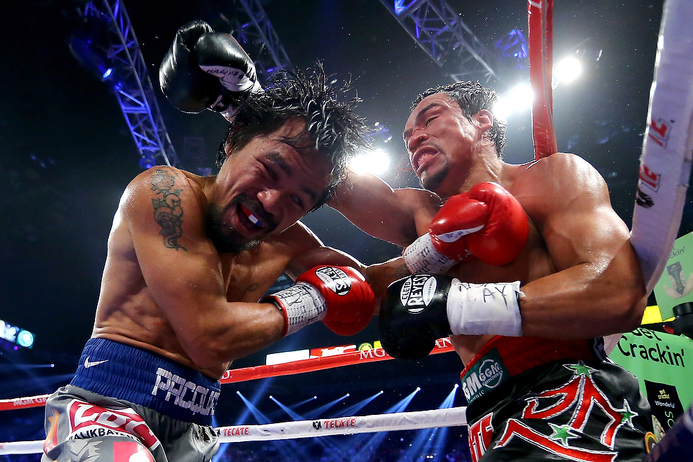 . Manny Pacquiao, left, and Juan Manuel Marquez exchange blows during their welterweight bout at the MGM Grand Garden Arena on December 8, 2012 in Las Vegas, Nevada.  (Photo by Al Bello/Getty Images)