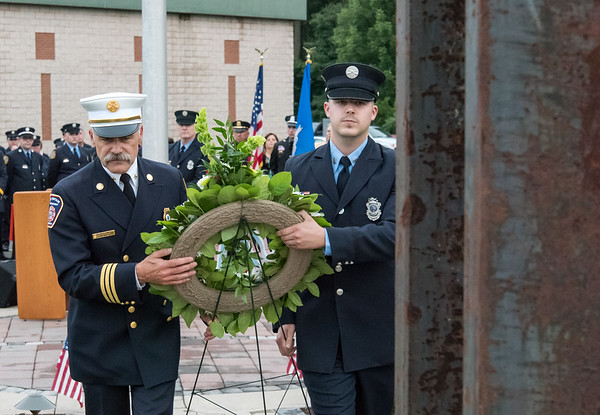 09/11/18 Wesley Bunnell | Staff Berlin officially dedicated its 9/11 Memorial in front of the Kensington Fire Department on Tuesday afternoon featuring steel beams from the World Trade Center. Friend of Berlin Fire Department New Britain Deputy Chief Paul Walsh, L, helps carry a wreath with his son Kensington Firefighter Tyler Walsh.