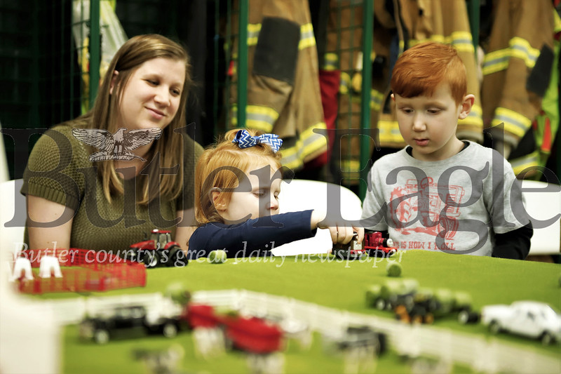 Megan McCall of West Sunbury watches her daughter Eleanor,2, and son Wyatt, 4, play with a model farm at the Butler Fire Department Toy Farm Show Saturday. Seb Foltz/Butler Eagle
