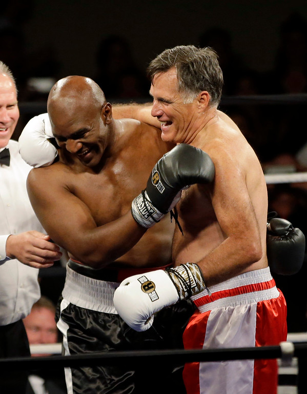 . Former Republican presidential candidate Mitt Romney and five-time heavyweight boxing champion Evander Holyfield celebrate after sparring during a charity fight night event Friday, May 15, 2015, in Salt Lake City. The black-tie event will raise money for the Utah-based organization CharityVision, which helps doctors in developing countries perform surgeries to restore vision in people with curable blindness. (AP Photo/Rick Bowmer)