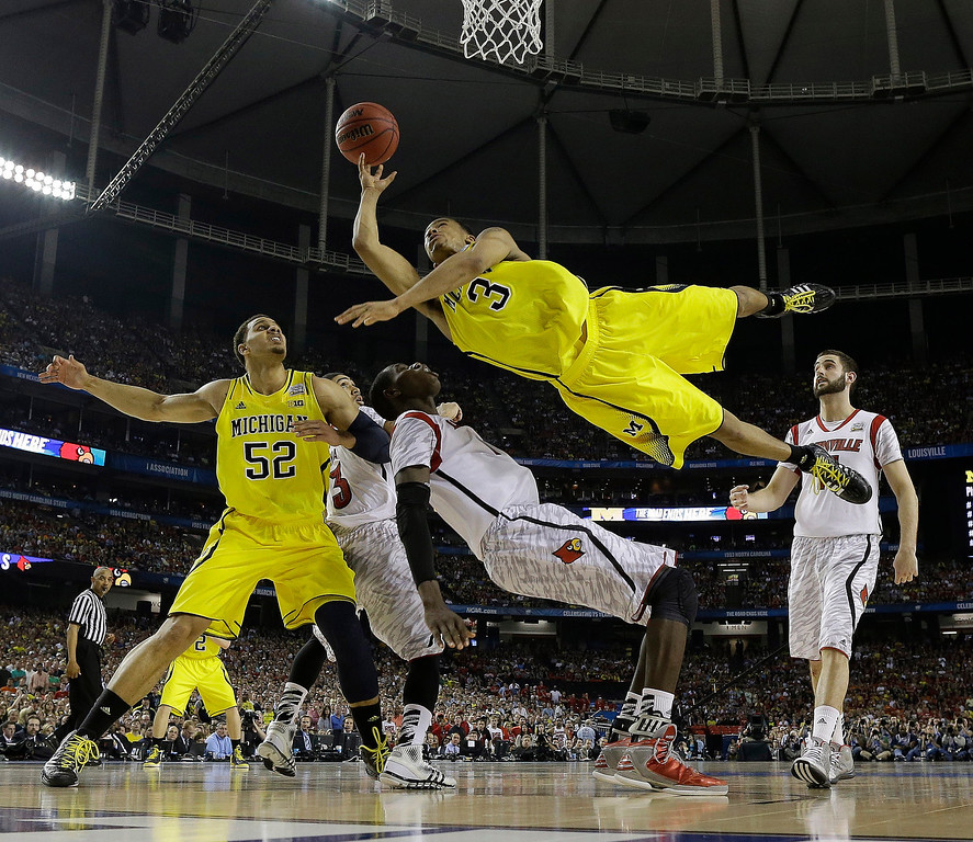 . Michigan guard Trey Burke (3) shoots over Louisville center Gorgui Dieng (10) during the second half of the NCAA Final Four tournament college basketball championship game Monday, April 8, 2013, in Atlanta. (AP Photo/Charlie Neibergall, File)