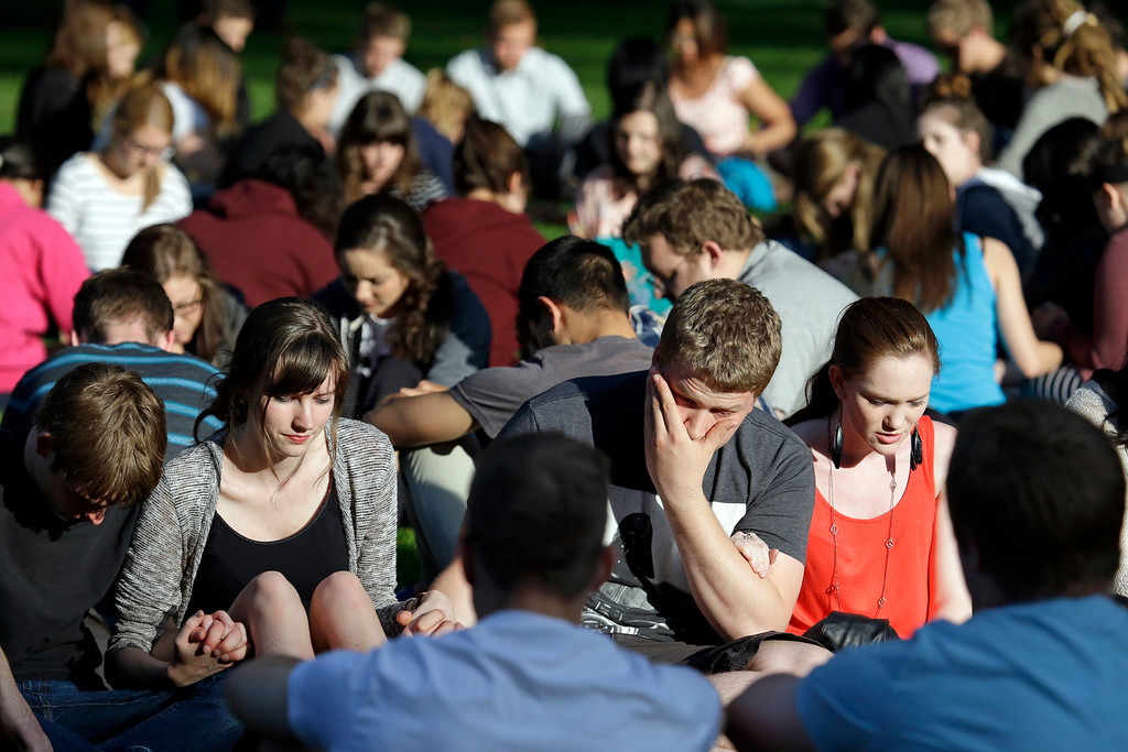 . Students from Seattle Pacific University gather outside in a prayer circle after a church service was full following a shooting on the university campus Thursday, June 5, 2014, in Seattle. A lone gunman armed with a shotgun and a knife opened fire in a building on the campus, killing one person before he was subdued with pepper spray by a student as he tried to reload, police said. (AP Photo/Elaine Thompson)