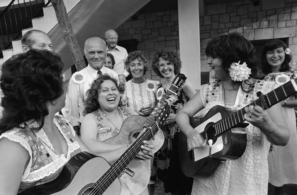 . Presidential hopeful John Glenn and his wife, Annie, are serenaded by a mariachi group called the Trio Harmonica at a party and political cartoon auction in San Antonio, Saturday, July 9, 1983. The event was held in conjunction with the National Women\'s Political Caucus. (AP Photo)