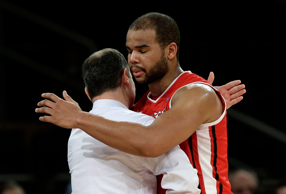 . Rutgers\' Austin Johnson hugs head coach Mike Rice during the second half of an NCAA college basketball game against Notre Dame at the Big East Conference tournament, Wednesday, March 13, 2013, in New York. Notre Dame won 69-61. (AP Photo/Frank Franklin II)