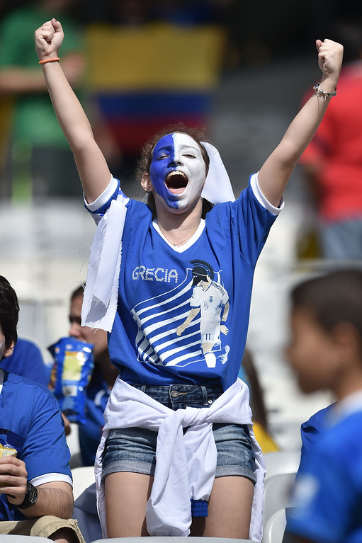. A fan of Greece cheers before a Group C football match between Colombia and Greece at the Mineirao Arena in Belo Horizonte during the 2014 FIFA World Cup on June 14, 2014.    AFP PHOTO / ARIS MESSINIS
