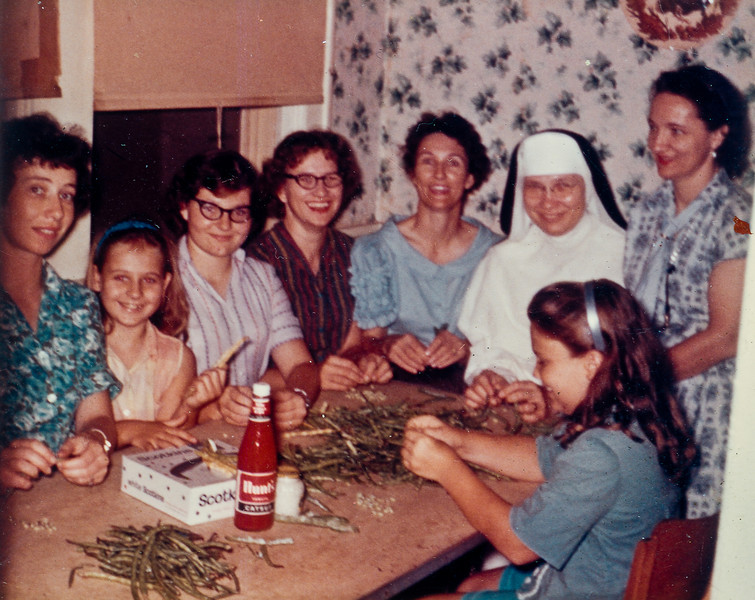 Shelling peas.  Left to right: Mary Jacob, Jan Smock, Sharon Curry, Maria Smock, Frieda Wick, Sister Clara Jacob, Daria Curry, Barbara Wick.  July 1961