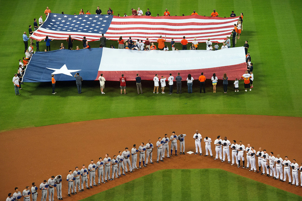 . Houston Astros and Texas Rangers players observe a moment of silence for the victims of the Sandy Hook Elementary School shooting as the United States and Texas state flags are displayed in centerfield before a season-opening baseball game at Minute Maid Park, Sunday, March 31, 2013, in Houston. (AP Photo/Houston Chronicle, Smiley N. Pool)