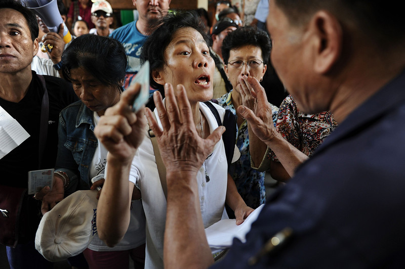 . A frustrated Thai voter (C) holds her national identification card as she shouts at police blocking the entrance to a polling station as voting was cancelled after anti-government protesters prevented the delivery of election material in downtown Bangkok on February 2, 2014.  Anti-government protesters blocked voting in dozens of constituencies in tense Thai elections on February 2 overshadowed by pre-poll bloodshed, an opposition boycott and fears of protracted political limbo.  (CHRISTOPHE ARCHAMBAULT/AFP/Getty Images)