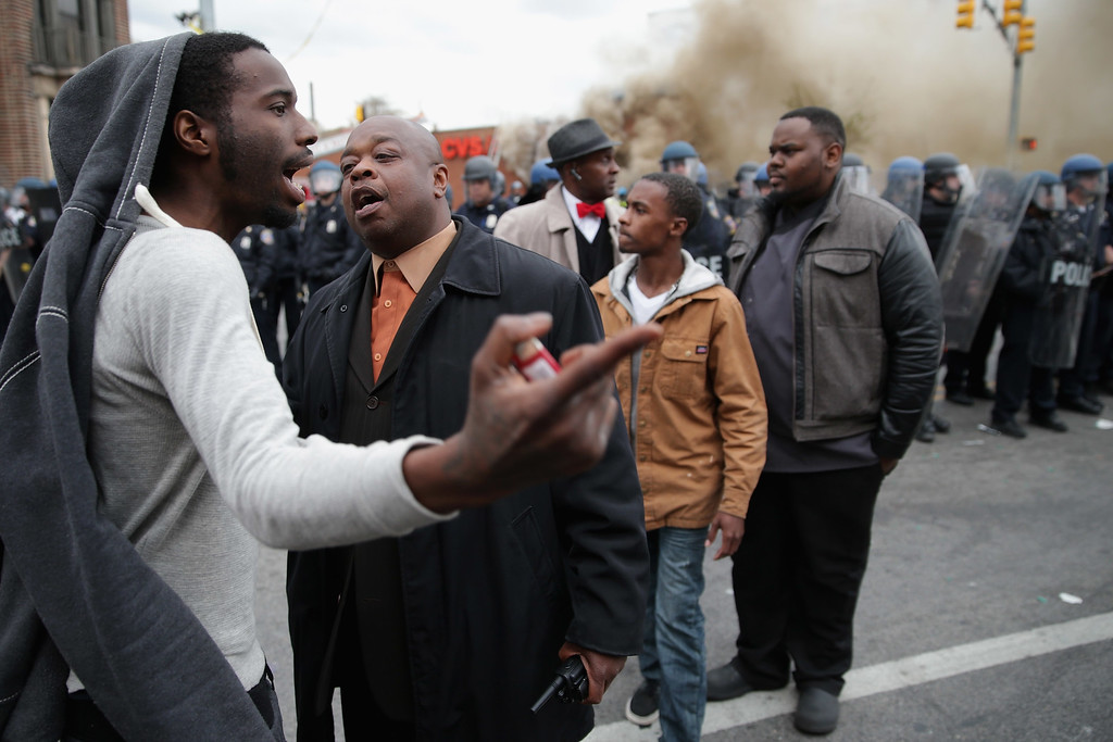 . BALTIMORE, MD - APRIL 27:  Two men argue opposing views as a CVS pharmacy burns at the corner of Pennsylvania and North avenues during violent protests following the funeral of Freddie Gray April 27, 2015 in Baltimore, Maryland. Gray, 25, who was arrested for possessing a switch blade knife April 12 outside the Gilmor Homes housing project on Baltimore\'s west side. According to his attorney, Gray died a week later in the hospital from a severe spinal cord injury he received while in police custody.  (Photo by Chip Somodevilla/Getty Images)