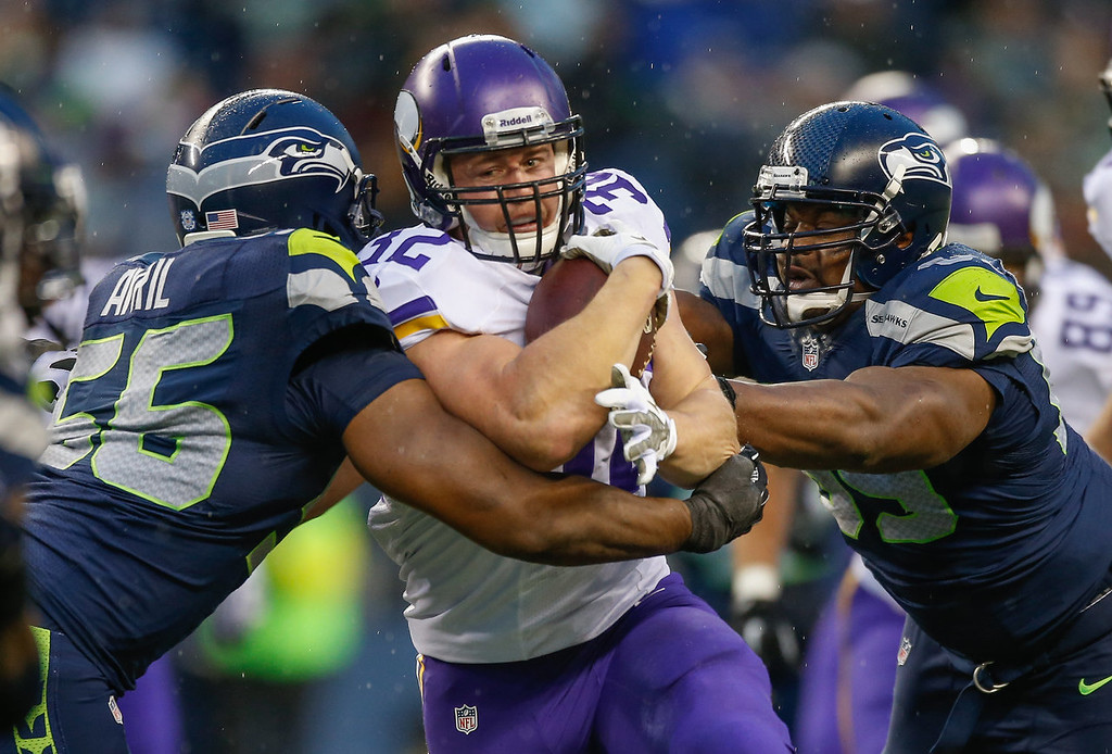 . Running back Toby Gerhart #32 of the Minnesota Vikings rushes against defensive end Cliff Avril #56 of the Seattle Seahawks at CenturyLink Field on November 17, 2013 in Seattle, Washington. The Seahawks defeated the Vikings 41-20.  (Photo by Otto Greule Jr/Getty Images)