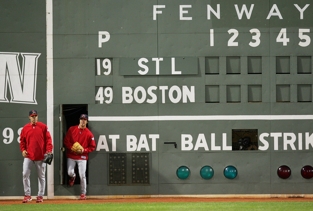 """. St. Louis Cardinals\' Matt Morris, left, and Danny Haren emerge from inside the \""""Green Monster\"""" wall in left field at Fenway Park in Boston, Friday Oct. 22, 2004 during a team workout. The Cardinals are preparing for Saturday\'s Game 1 of the World Series against the Boston Red Sox. (AP Photo/Winslow Townson)"""
