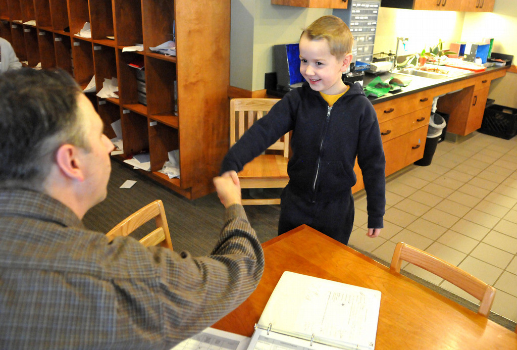 . Shaking hands with the teacher is a big part of the start of each Montessori student\'s day. Lower Elementary student, Sebastian Hansen, 6, is greeted by his teacher John Albright before the start of class.   (Pioneer Press: John Doman)