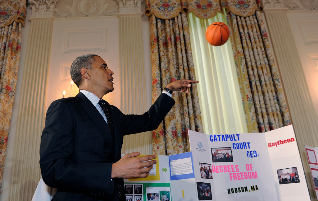 . President Barack Obama tosses a basketball as he tours the 2014 White House Science Fair exhibits that are on display in the State Dining Room at the White House in Washington, Tuesday, May 27, 2014. Students from Hudson, Mass., showed Obama their basketball catapult. (AP Photo/Susan Walsh)