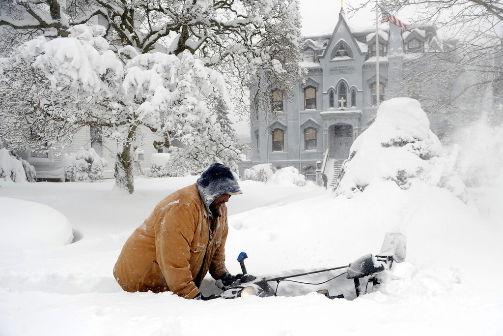 . George Ransom pushes his snowthrower on the sidewalk along Broadway in front of St. Patrick\'s School, Saturday, Feb. 9, 2013, after a snow storm in Norwich, Conn. (AP Photo/The Day, Sean D. Elliot)