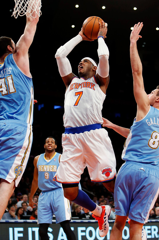 . New York Knicks\' Carmelo Anthony (7) shoots against Denver Nuggets\' Kosta Koufus (41) and Danilo Gallinari (8) during the first half of an NBA basketball game, Sunday, Dec. 9, 2012, in New York. (AP Photo/Jason DeCrow)