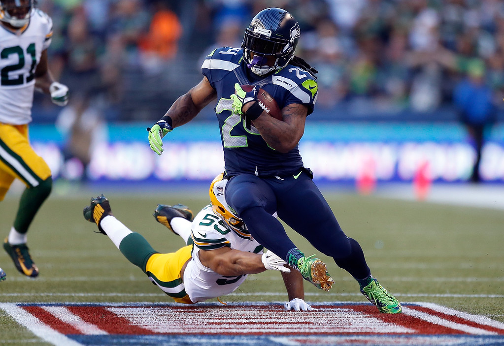 . SEATTLE, WA - SEPTEMBER 04: Running back Marshawn Lynch #24 of the Seattle Seahawks runs with the ball as linebacker Brad Jones #59 of the Green Bay Packers dives in an attempt to catch him during the second quarter of the game at CenturyLink Field on September 4, 2014 in Seattle, Washington.  (Photo by Otto Greule Jr/Getty Images)