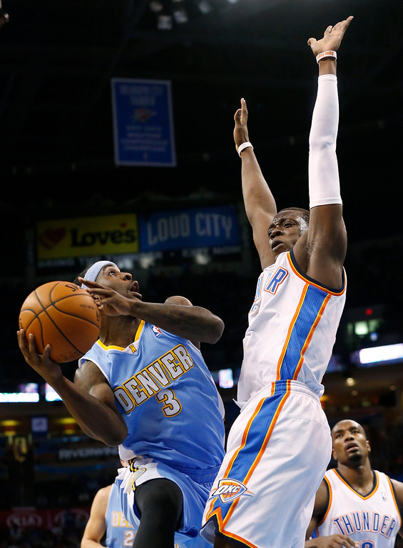 . Denver Nuggets guard Ty Lawson (3) shoots as Oklahoma City Thunder guard Reggie Jackson (15) defends in the first quarter of an NBA basketball game in Oklahoma City, Monday, March 24, 2014. (AP Photo/Sue Ogrocki)