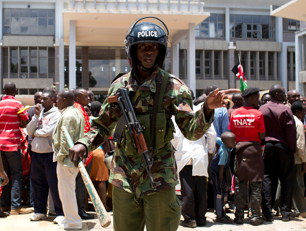 . Riot policeman keep watch over supporters of presidential candidate Uhuru Kenyatta as they wait for him to show up and give a speech in Nairobi March 9, 2013.  REUTERS/Siegfried Modola