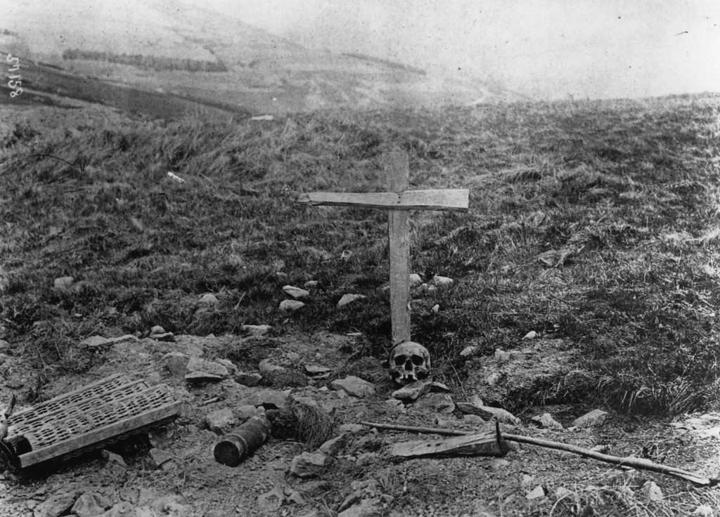 . June 1915:  The grave of a German soldier, marked by a simple wooden cross and a skull.  (Photo by Hulton Archive/Getty Images)
