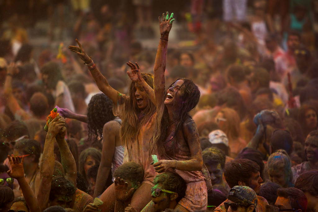 . Revelers dance after throwing special colored powders on each other during a Monsoon Holi Festival in Madrid, Spain, Saturday, Aug. 9, 2014. The festival is based on the Hindu spring festival Holi, also known as the festival of colors where participants color each other with dry powder and colored water. (AP Photo/Andres Kudacki)