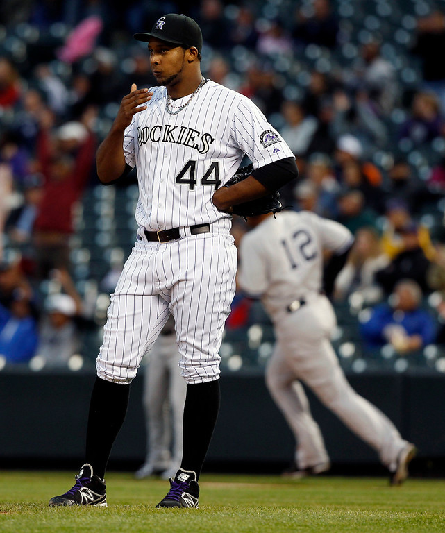 . Colorado Rockies starting pitcher Juan Nicasio, front, reacts as New York Yankees\' Vernon Wells, rear, rounds the bases on his two-run home run in the first inning of a baseball game in Denver on Wednesday, May 8, 2013. (AP Photo/David Zalubowski)