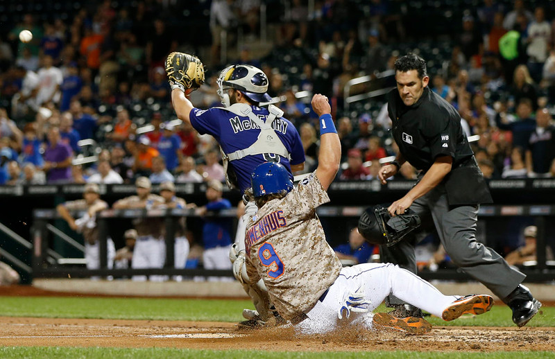 . The throw comes in too late for Colorado Rockies catcher Michael McKenry (8) to make a play as New York Mets Kirk Nieuwenhuis (9) scores on Lucas Duda\'s first inning double in a baseball game against the Colorado Rockies in New York, Monday, Sept. 8, 2014. (AP Photo/Kathy Willens)