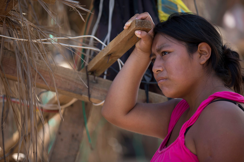 . A woman pauses as she leans against a wooden slat that is part of her home destroyed by Hurricane Odile, in San Jose de los Cabos, Mexico, Thursday, Sept. 18, 2014. Water and electricity service remained out and phone service was intermittent. Electric commission officials said some 2,500 power poles were toppled by Odile, which struck late Sunday as a Category 3 storm. (AP Photo/Dario Lopez-Mills)