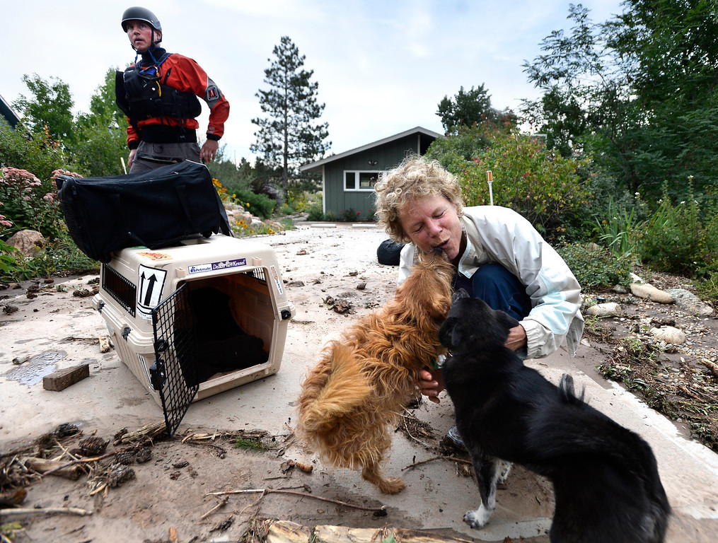 . Suzanne Sophocles hugs her dogs after they were all rescued from her flooded home, Friday, Sept. 13, 2013 in Boulder, Colo. By truck and helicopter, thousands of people stranded by floodwaters came down from the Colorado Rockies on Friday, two days after seemingly endless rain turned normally scenic rivers and creeks into coffee-colored rapids that wrecked scores of roads and wiped out neighborhoods. (AP Photo/The Daily Camera, Jeremy Papasso) NO SALES
