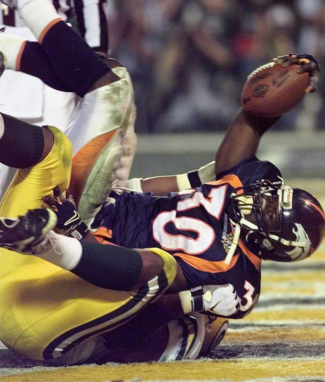 . Denver Broncos running back Terrell Davis holds up the ball after he crosses the end zone to score in the second half of Super Bowl XXXII at San Diego\'s Qualcomm Stadium Sunday, Jan. 25, 1998. (AP Photo/Ed Reinke)