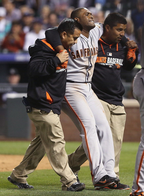 . San Francisco Giants relief pitcher Santiago Casilla, center, is helped off the field after injuring himself while running out a ground ball against the Colorado Rockies in the ninth inning of the Giants\' 5-1 victory in a baseball game in Denver on Wednesday, May 21, 2014. (AP Photo/David Zalubowski)