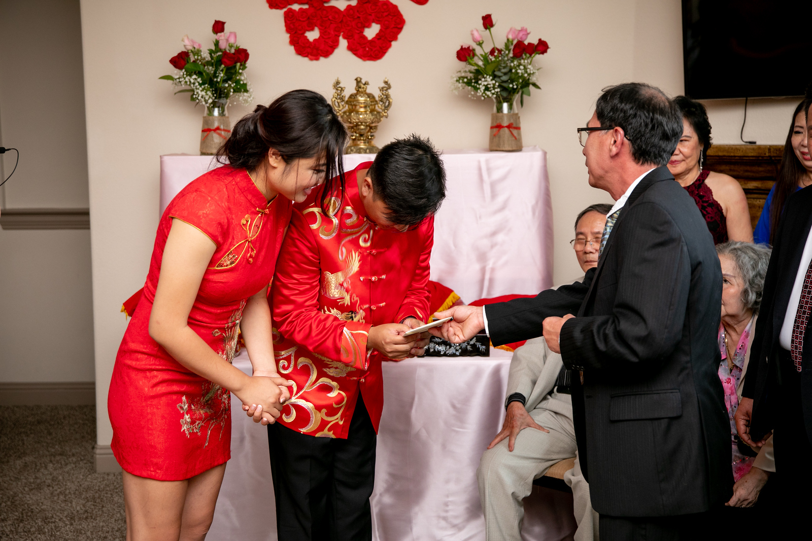 A bride and groom bowing to a man giving them an envelope