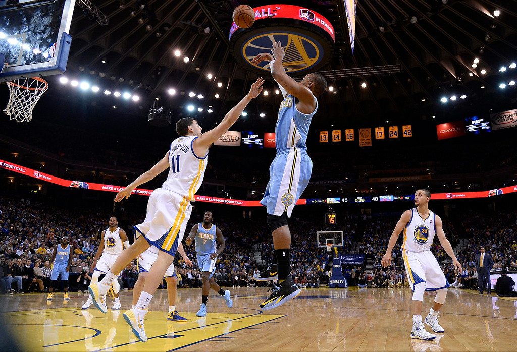. epa04023510 Denver Nuggets shooting guard Randy Foye (C) shoots over Golden State Warriors shooting guard Klay Thompson (L) during the first half of their NBA game at Oracle Arena in Oakland, California, USA, 15 January 2014.  EPA/JOHN G. MABANGLO CORBIS OUT