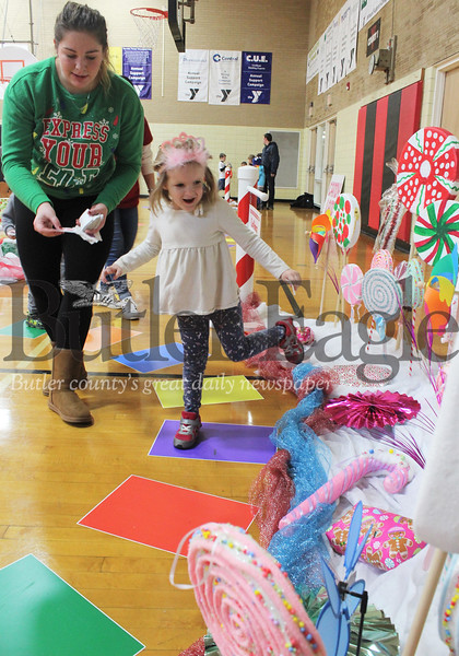Harold Aughton/Special to the Eagle: Alexandra Dubyak, 5, of Butler skips through the Lollipop Woods with volunteer Veronica Brown during a game of Candy Land at the Butler YMCA.