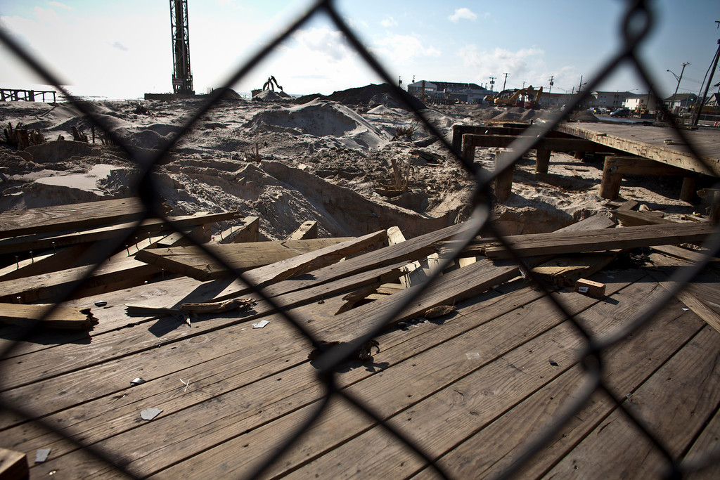 . Damaged wood planks sit behind a fence as the Seaside Heights boardwalk and amusement park remains under construction one year after being partially destroyed by Superstorm Sandy in October 2012, and damaged again in September 2013 by an electrical fire, on October 29, 2013 in Seaside Heights, New Jersey.   (Photo by Kena Betancur/Getty Images)