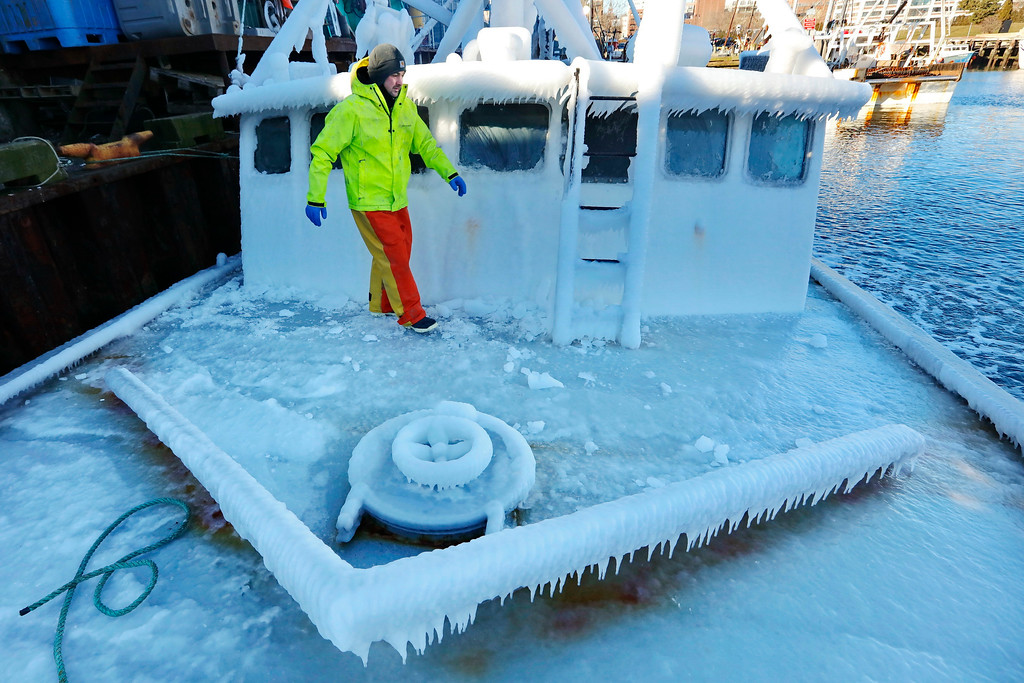 . With temperatures in the single digits, Ray Levesque, mate of the crab/lobster boat Bradbill, makes his way across the deck covered in ice to tie off, after arriving in New Bedford, Mass., harbor on Thursday, Dec. 28, 2017, from a one day fishing voyage. Temperatures across Massachusetts are not expected to rise above freezing for days. (Peter Pereira/Standard Times via AP)