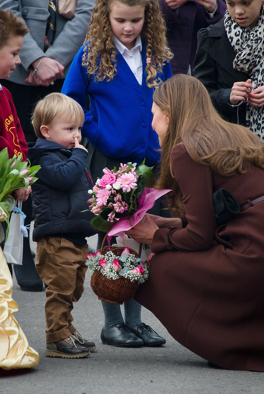 . A young boy picks his nose as he talks to Catherine, Duchess of Cambridge during her visit to Peaks Lane fire station in Grimsby, northern England on March 5, 2013.  The Duchess of Cambridge is on an official visit to Grimsby during which she visited the National Fishing Heritage Centre and will meet with unemployed teenagers.  Photo credit should read LEON NEAL/AFP/Getty Images