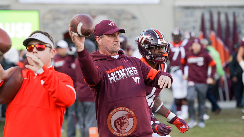Hokies DC Bud Foster throws a football to his players going through pre-game warmups. (Mark Umansky/TheKeyPlay.com)
