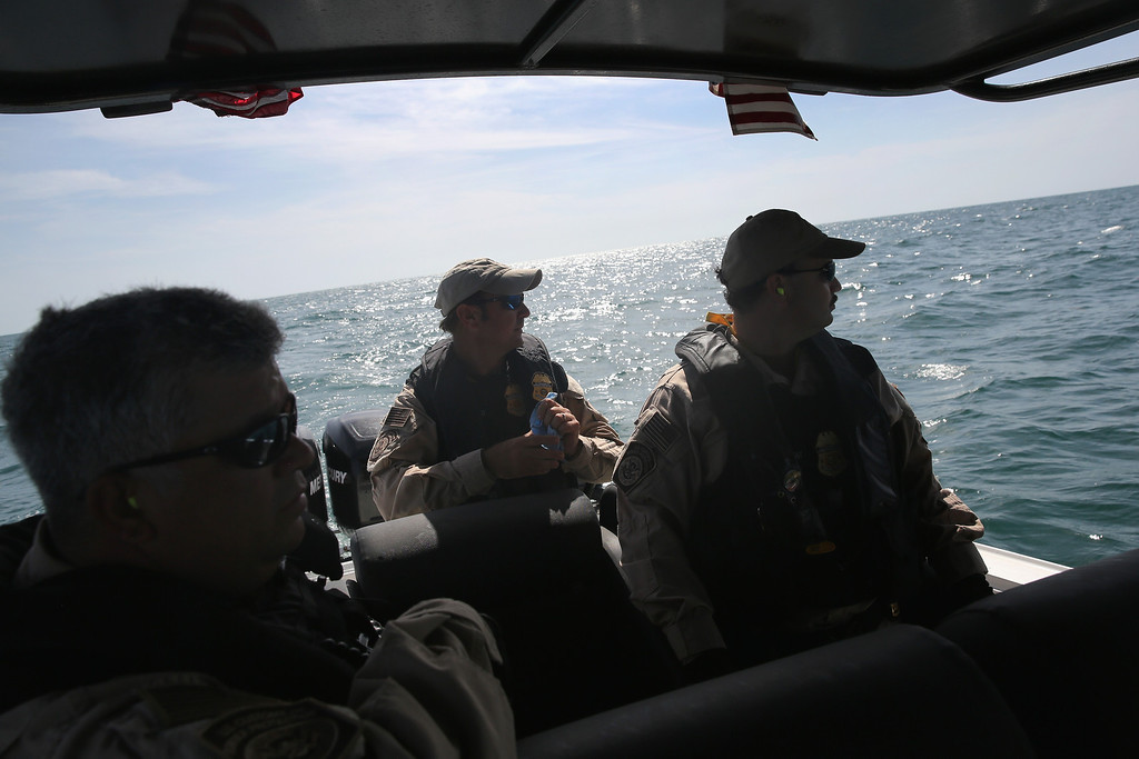 . PORT ISABEL, TX - APRIL 12:  A boat crew from the U.S. Office of Air and Marine (OAM) looks towards a suspicious boat just across the Mexican border in the Gulf of Mexico on April 12, 2013 near Port Isabel, Texas. The crew patrols coastline waters near the U.S.-Mexico border searching for drug smugglers as well as illegal immigrants, which come across from Mexico near the mouth of the Rio Grande River. The Midnight Express interceptor is a 39 foot 900 horsepower craft capable of chasing smugglers down at 55 knots (63 mph). OAM units also push back illegal fishing boats out of U.S. waters.  (Photo by John Moore/Getty Images)