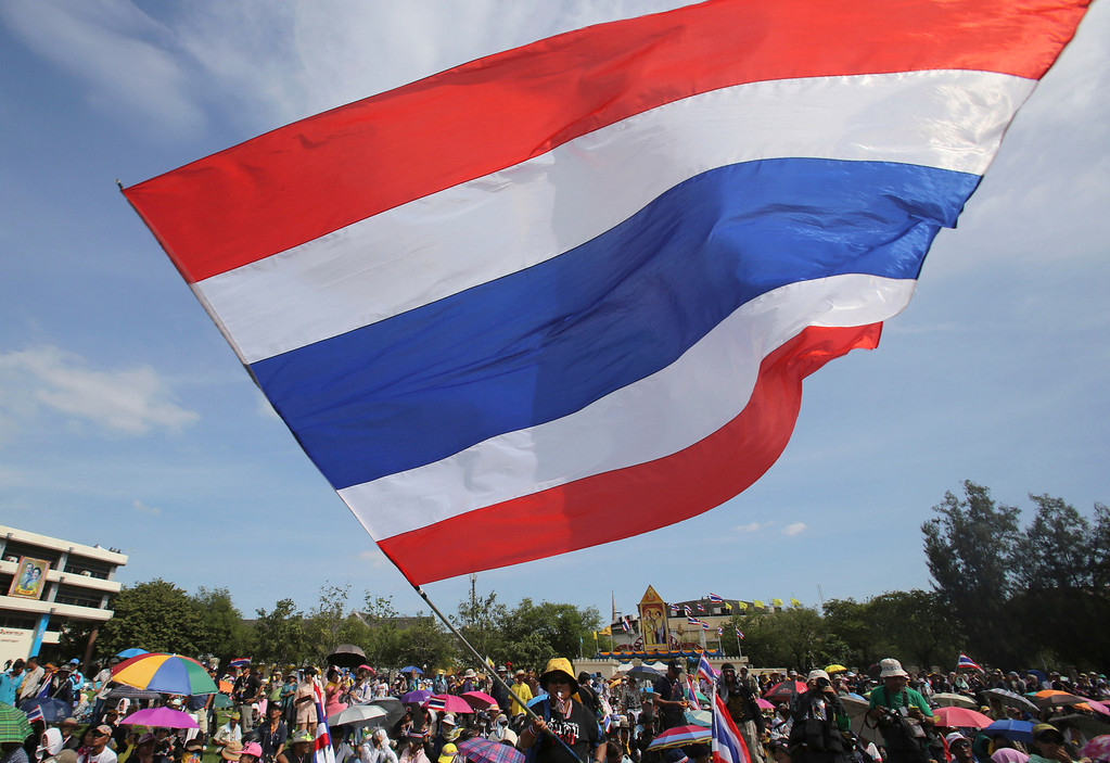 . An anti-government protester waves a Thai national flag at the Royal Thai Army compound compound in Bangkok, Thailand, Friday, Nov. 29, 2013. The protesters stormed into the national army headquarters on Friday, breaking into their latest high-profile target in a bid to topple Prime Minister Yingluck Shinawatra. (AP Photo/Sakchai Lalit)