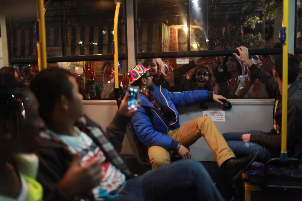 "Description of . People sitting on a bus look at made up and dressed up people gesturing in front of the window during the customary ""Zombie Walk\"" during the Jewish holiday of Purim in the Israeli coastal city ofTel Aviv on February 23, 2013. The carnival-like Purim holiday is celebrated with parades and costume parties to commemorate the deliverance of the Jewish people from a plot to exterminate them in the ancient Persian empire 2,500 years ago, as recorded in the Biblical Book of Esther. AFP PHOTO/DANIEL BAR"