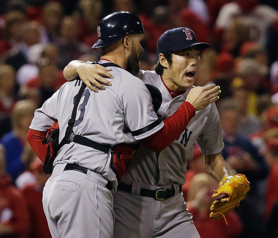 . Boston Red Sox relief pitcher Koji Uehara hugs catcher David Ross after getting St. Louis Cardinals\' Matt Holliday to fly out and end Game 5 of baseball\'s World Series Monday, Oct. 28, 2013, in St. Louis. The Red Sox won 3-1 to take a 3-2 lead in the series. (AP Photo/Jeff Roberson)