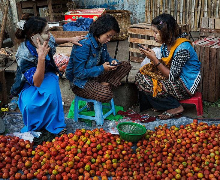 Young girls at the food market, more interested on social media than on selling apples.  Meiktila, Myanmar, 2017.