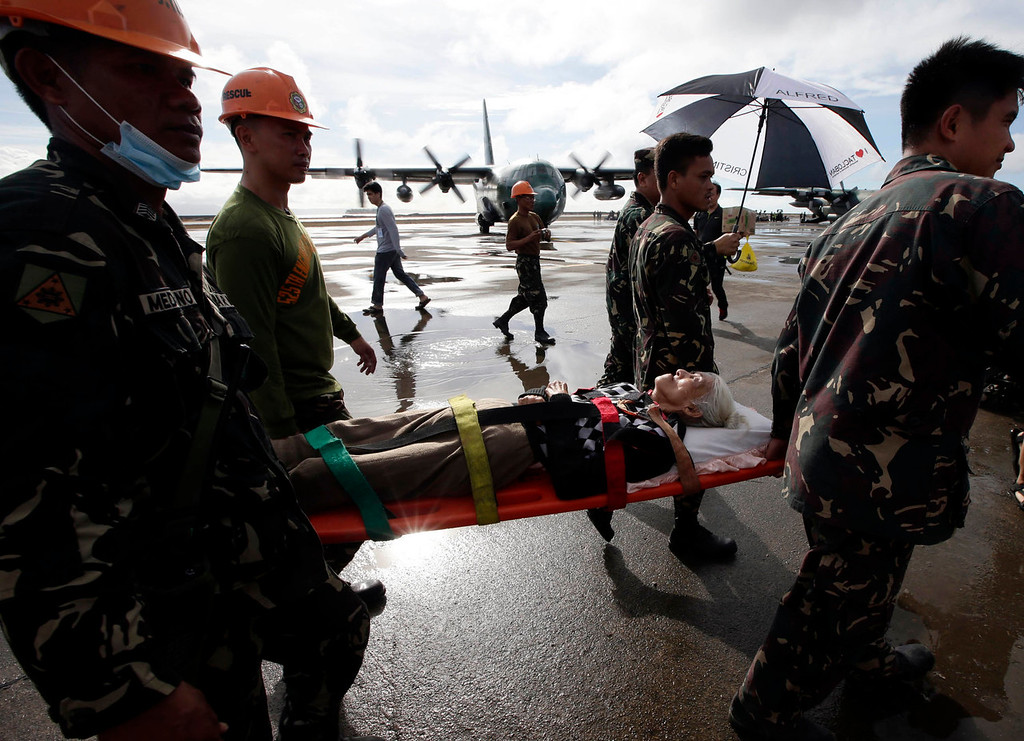 . An injured typhoon survivor is carried on a stretcher prior to being airlifted in a military transport plane Wednesday Nov. 13, 2013 from the damaged Tacloban airport  at Tacloban city, Leyte province in central Philippines. Typhoon Haiyan, one of the strongest storms on record, slammed into central Philippine provinces Friday, leaving a wide swath of destruction and thousands of people dead. (AP Photo/Bullit Marquez)