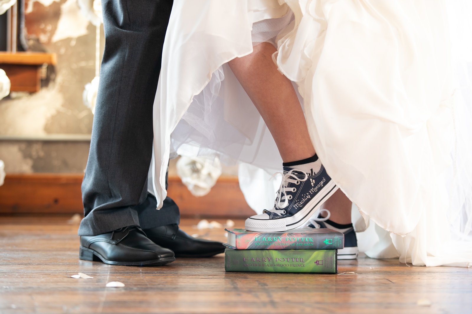bride and grooms feet - the bride with sneakers reading mischief managed while standing on two Harry Potter books