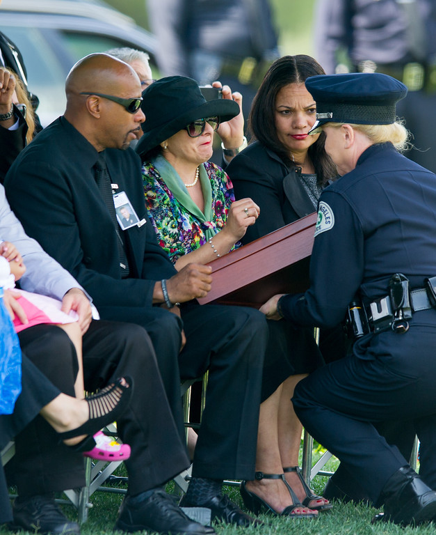 . LAPD Capt. Maureen Ryan gives a flag case to Lillie Price at the burial of LAPD officer Chris Cortijo, Tuesday, April 22, 2014, at Forest Lawn Hollywood Hills. (Photo by Michael Owen Baker/L.A. Daily News)