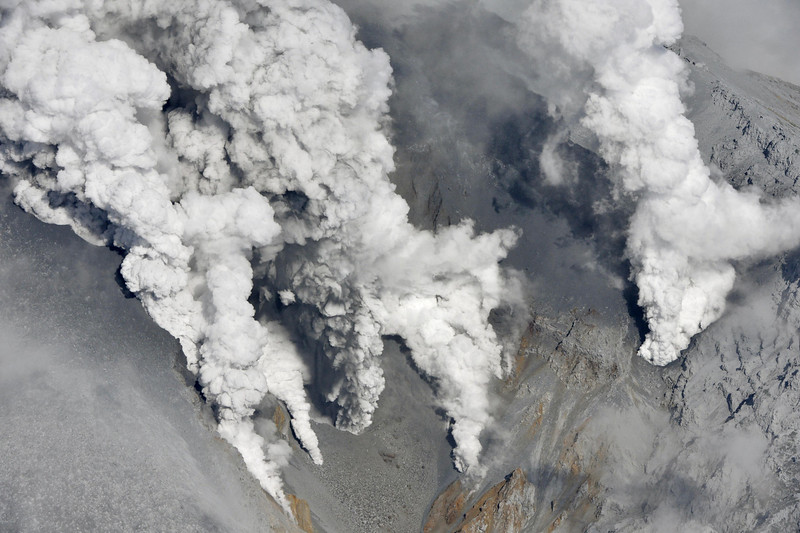 . Dense fumes are spewed out from several spots on the slope of Mt. Ontake as the volcano erupts in central Japan Saturday, Sept. 27, 2014. Mt. Ontake erupted Saturday, sending a large plume of ash high into the sky and prompting a warning to climbers and others to avoid the area. Japanese broadcaster NHK, citing local authorities, said there were reports of injuries, but no word on their severity.  (AP Photo/Kyodo News)
