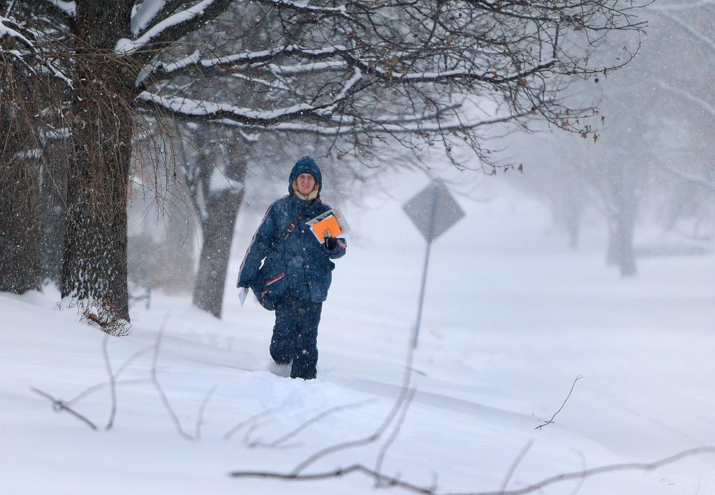 . A letter carrier walks through the snow while delivering mail Tuesday, Feb. 4, 2014, in Topeka, Kan. (AP Photo/Topeka Capital-Journal, Chris Neal)